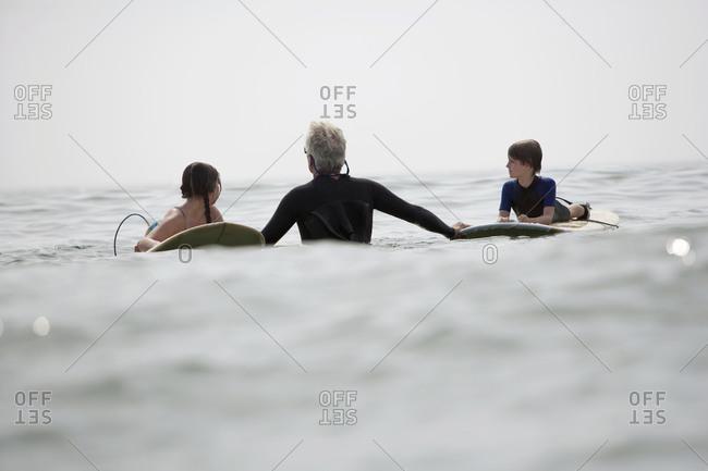 A grandfather teaches grandchildren how to surf