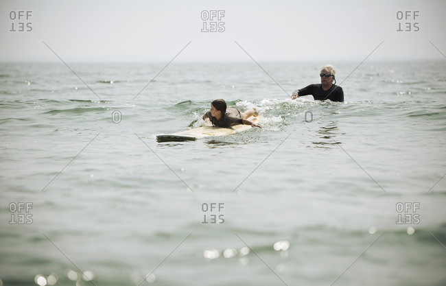 A grandfather helps a young girl learn to surf