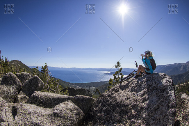 Woman mountain biking resting on rock