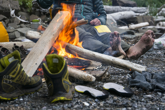Man drying shoes and feet by fire in Aniakchak, AK