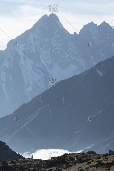 Lone man sitting among mountain peeks