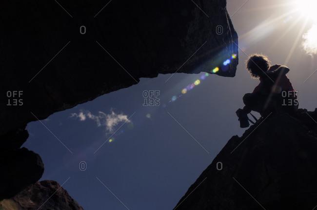 Backlit climber among the rocks