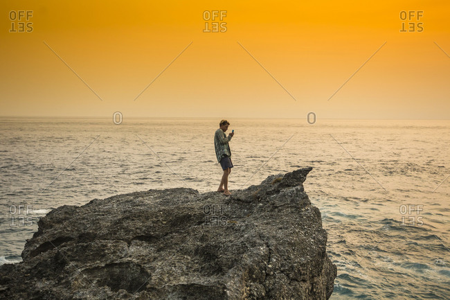Man standing on coastline taking a picture of the ocean