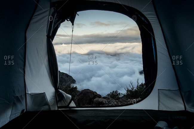 View from inside a tent placed on a mountain top over the clouds