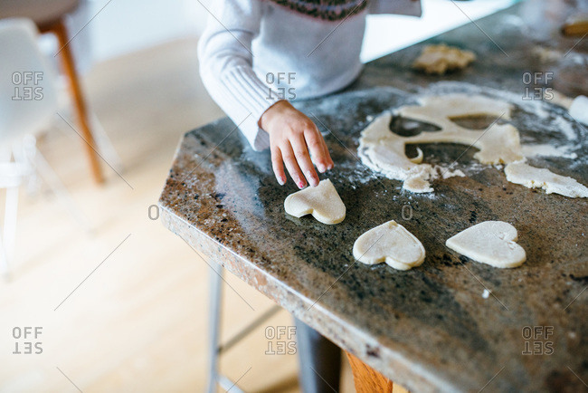 Girl making Valentine heart cookies