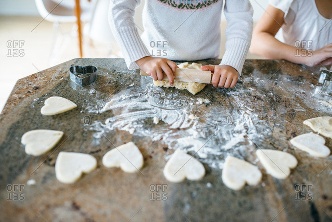 Girl making Valentine heart shaped cookies