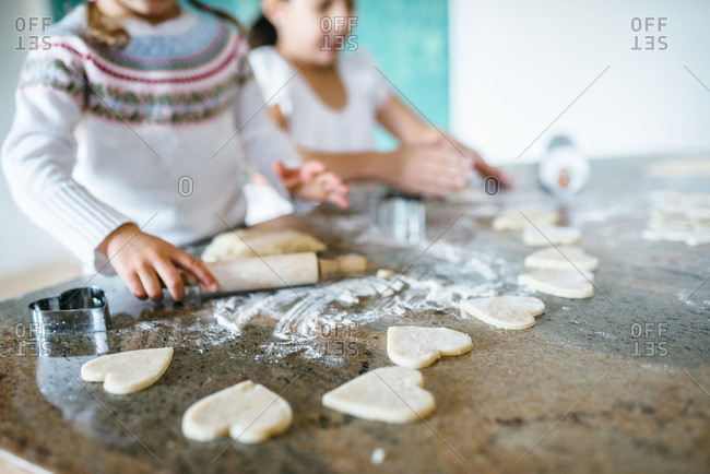 Girls making Valentine heart cookies together