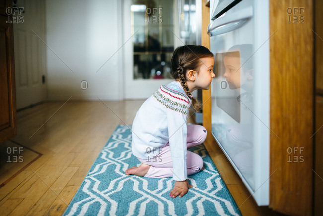 Girl watching her cookies bake in an oven