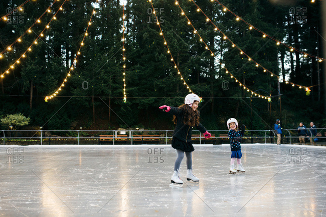 Children ice skating at an outdoor rink