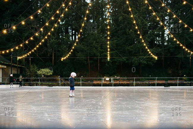 Little girl ice skating on a rink outdoors