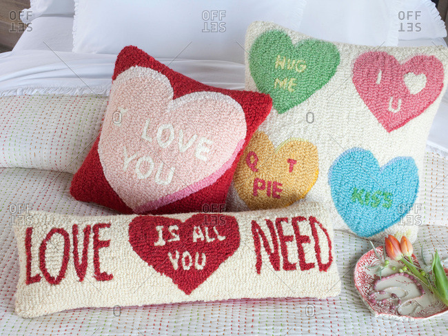 Knot pillows with romantic sayings on a bed
