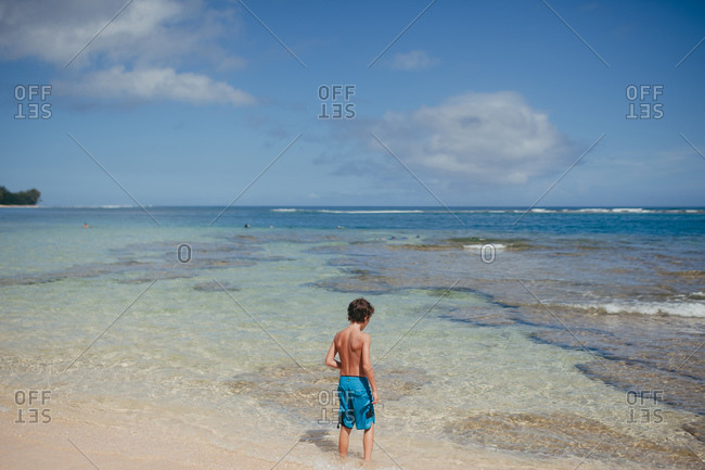 Little boy standing in clear waters on a tropical beach