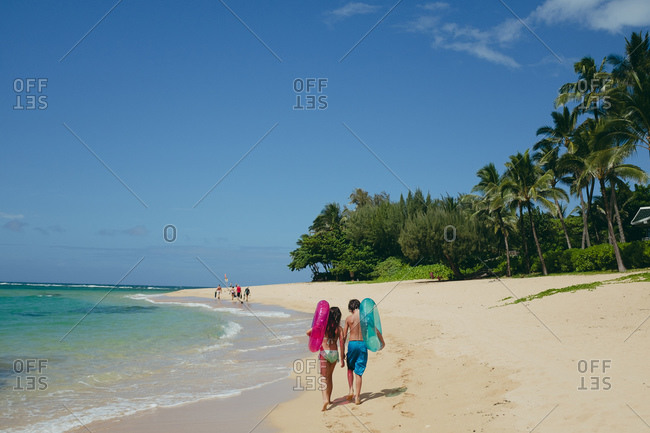 Brother and sister carrying inflatable floats on a beach
