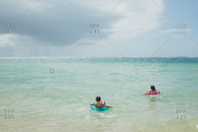 Brother And Sister Floating On Inner Tubes In The Ocean Stock Photo Offset