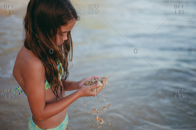 Little girl on a beach holding a handful of sand