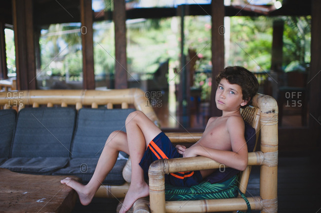 Little boy sitting in a bamboo beach chair