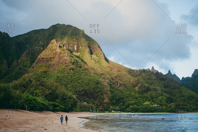 Boy and girl walking on a beach near a tall mountain