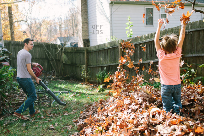 Boy playing in leaves as his dad uses a leaf blower