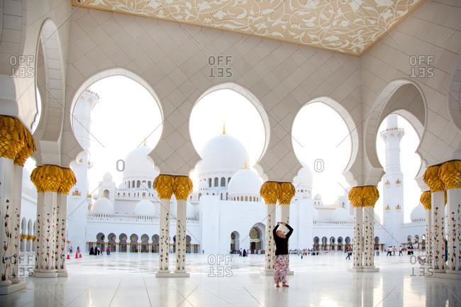 Abu Dhabi, UAE - September 14, 2012: Woman taking photo of ceiling decoration at Sheik Zayed Grand Mosque, UAE