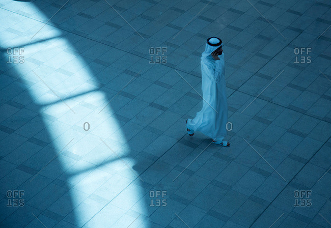 Dubai, UAE - September 16, 2012: Man on phone while walking through Burj Khalifa Mall in Dubai, UAE