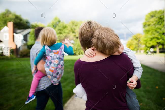 Parents holding their children on suburban sidewalk