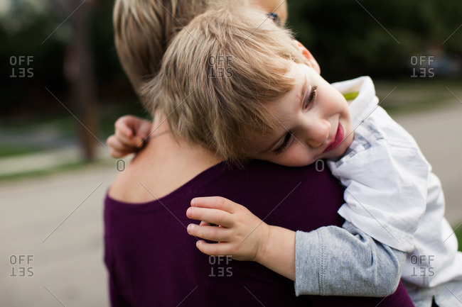 Boy hugging his mother while being carried