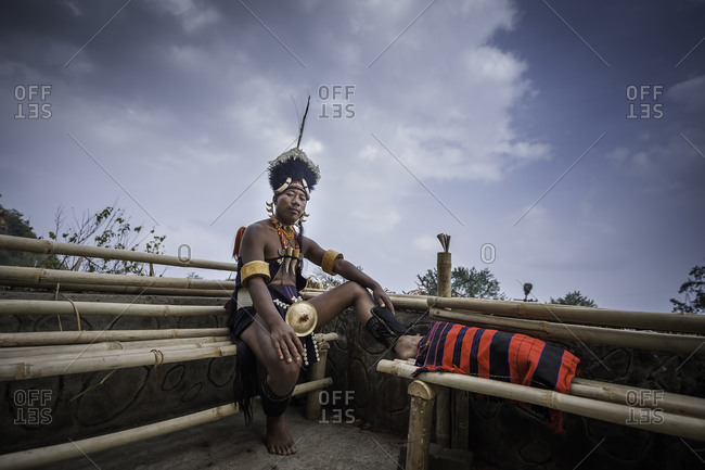 Nagaland, India - December 10, 2015: Portrait of a Naga man wearing traditional costume sitting on bamboo bench