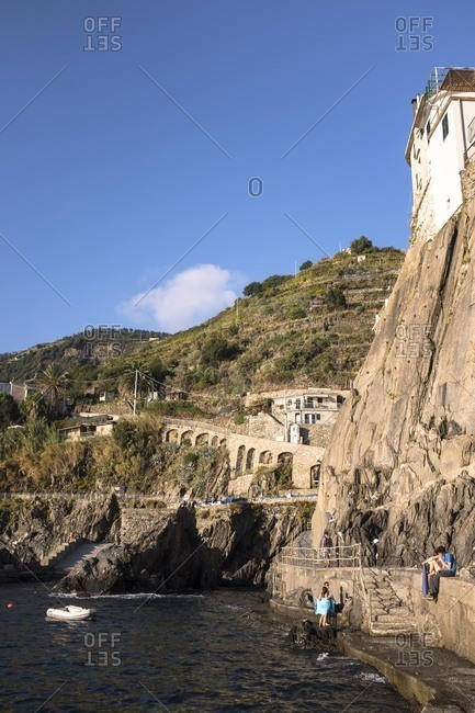 Cinque Terre, Italy - October 7, 2015: People swimming off of a cliff by a village in Cinque Terre, Italy