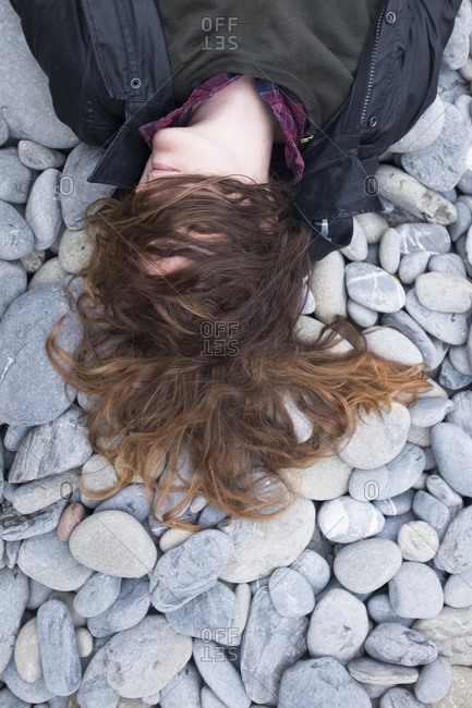 Woman lying on rocks with hair covering her face