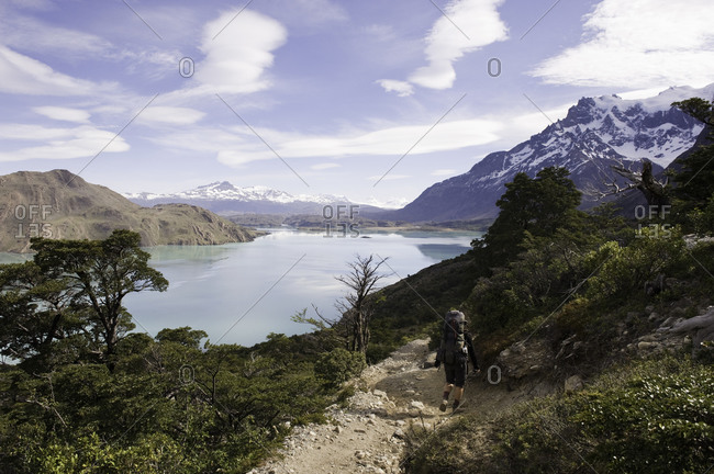 Backpacker on a mountain trail overlooking a lake