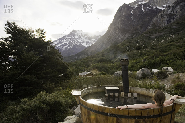 Woman resting in a hot tub overlooking a mountain view