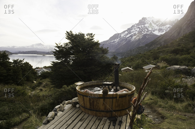 Woman relaxing in a wooden hot tub in the mountains