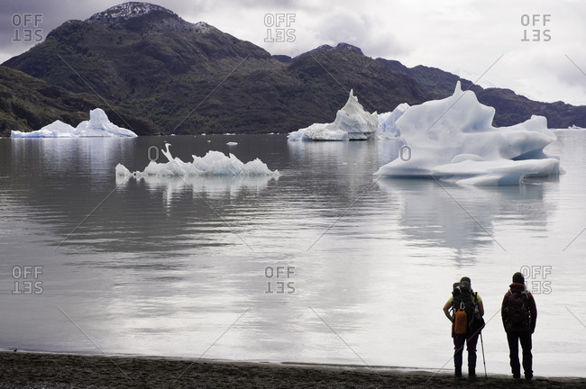 Backpackers looking at icebergs in a mountain lake
