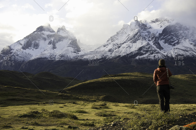 Woman standing in a field looking at snow-capped mountains