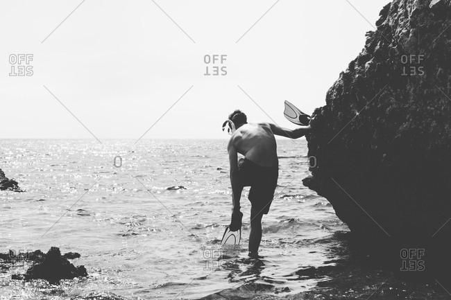 Young man putting flippers on his feet for scuba diving