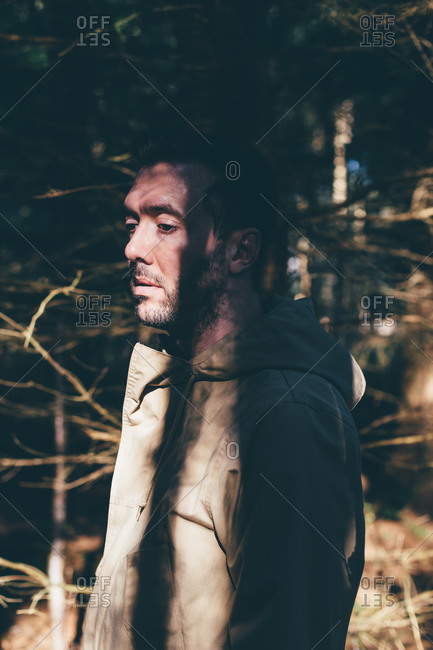 Sad man walking through woods