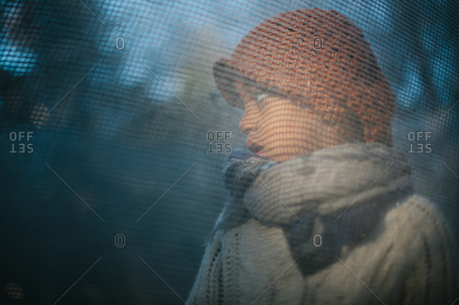 Little girl in a sweater and scarf standing behind a screen