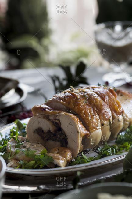 Stuffed turkey breast on platter on Thanksgiving table