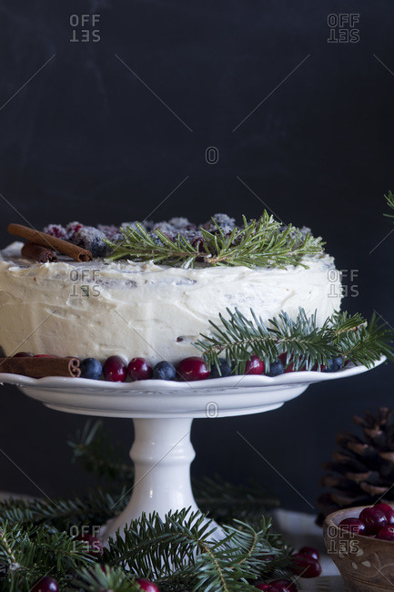 Christmas cake decorated with berries, cinnamon and evergreen