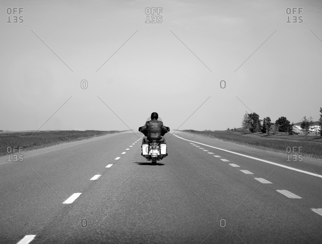 Lone person on motorcycle riding down the open highway in Alberta, Canada