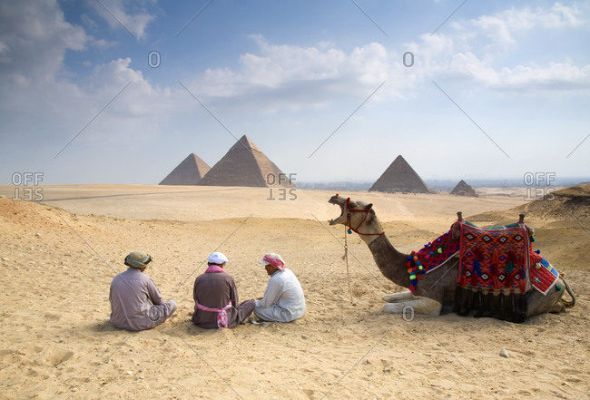 Giza, Egypt - October 11, 2008: Camel and guides resting on the sands before the pyramids of Giza, Egypt