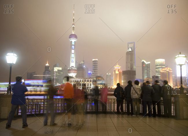 Blurred motion of people walking on the Bund in Shanghai, China at night