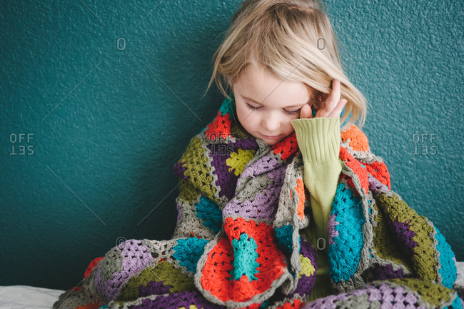 Little girl wrapped in a colorful blanket