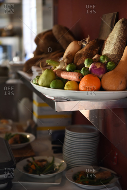 Fresh fruits and vegetables on a white platter on a kitchen shelf