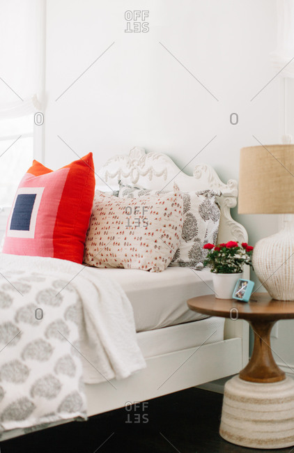 Round bedside table and white linens