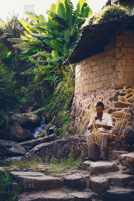 Asian man making a basket by hand
