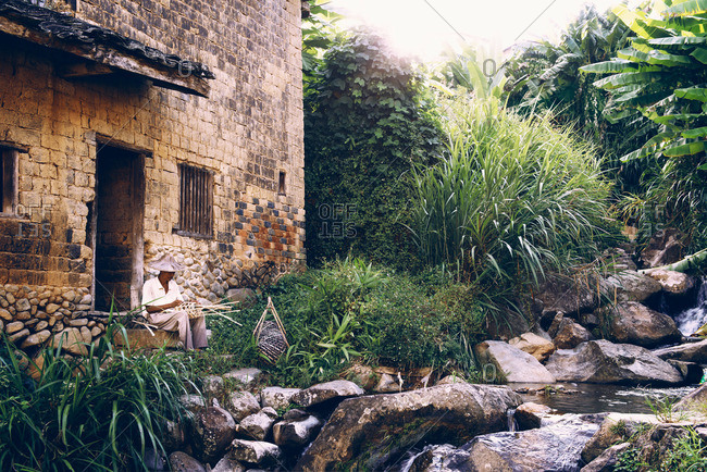 Asian man making a basket by hand next to a stream