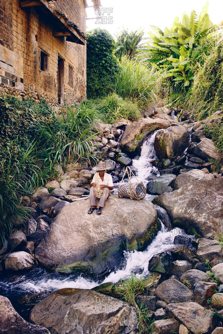 Asian man sitting by a waterfall making a basket by hand