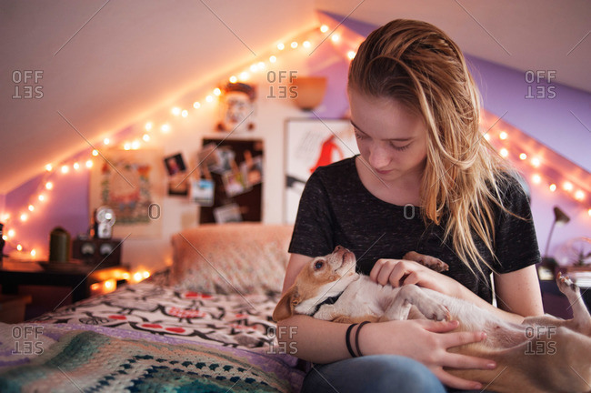 Teenager petting her dog in her room