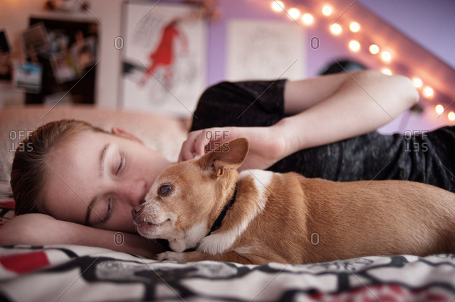 Teenager snuggling with her dog in her room